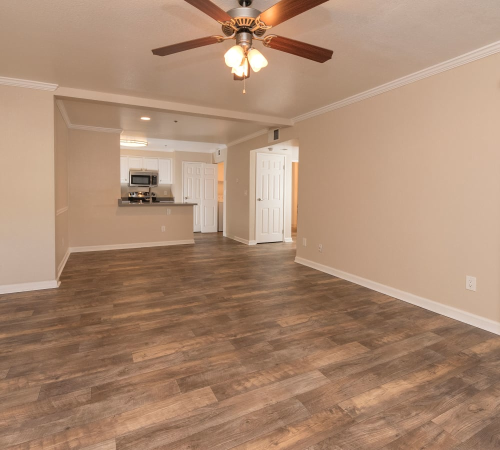 Living room with wood-style flooring and a ceiling fan at Sterling Heights Apartment Homes in Benicia, California