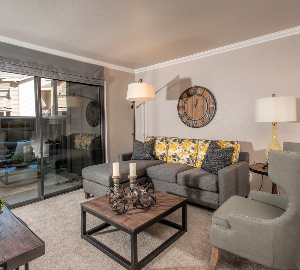 A comfortable and stylish living room with a private patio at Deer Valley Apartment Homes in Roseville, California