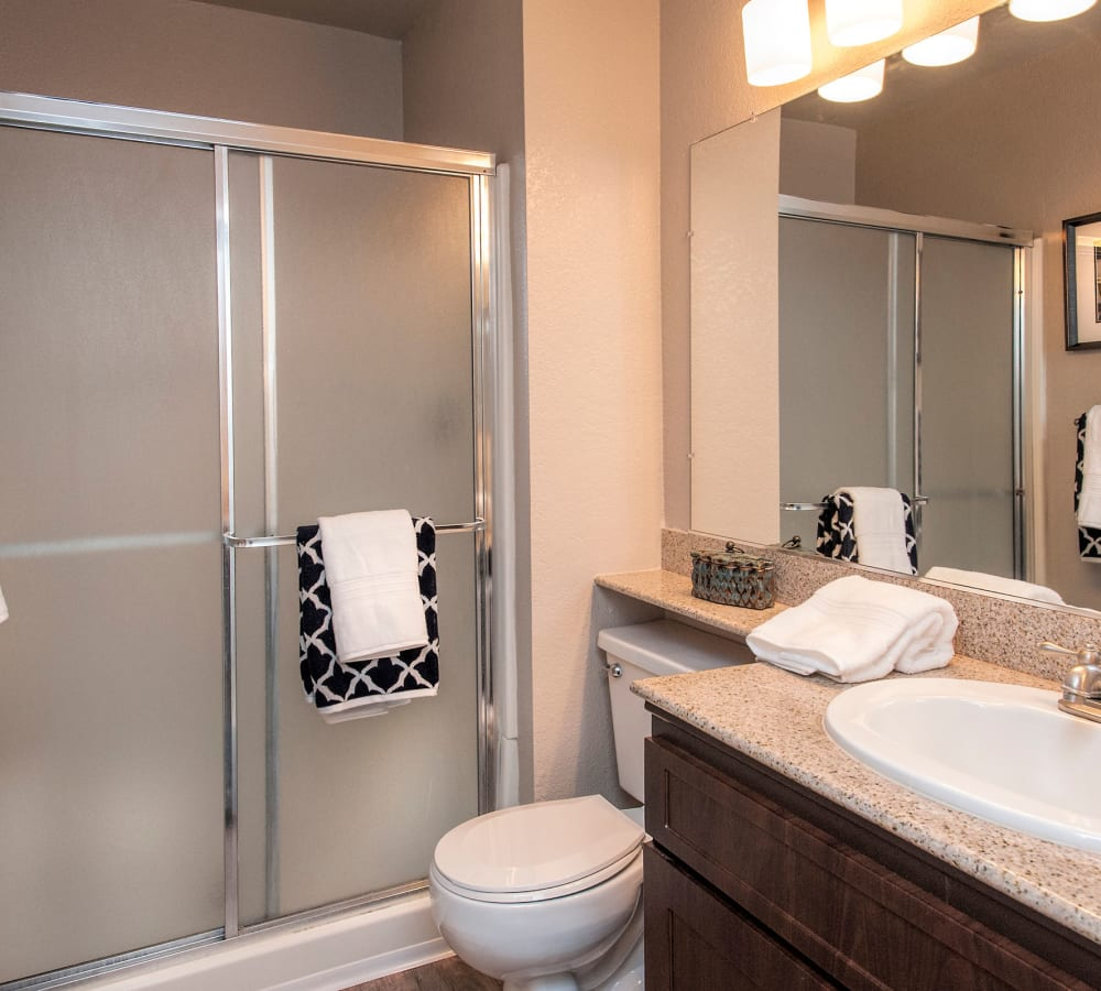 A bright bathroom with brown cabinetry at Deer Valley Apartment Homes in Roseville, California