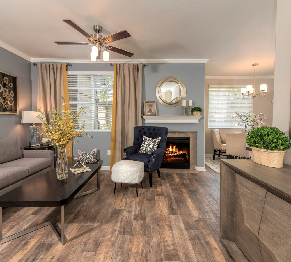Living room with wood-style flooring and a fireplace at The Artisan Apartment Homes in Sacramento, California