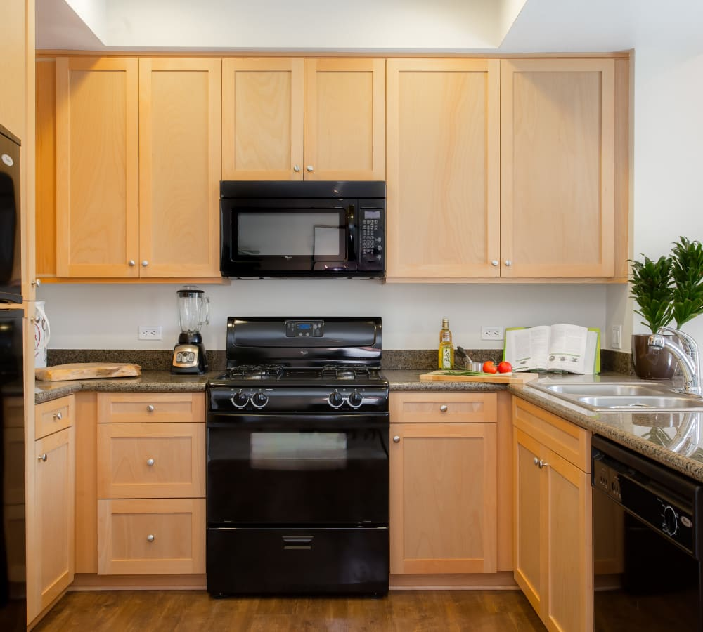 Kitchen with black appliances at Paragon at Old Town in Monrovia, California