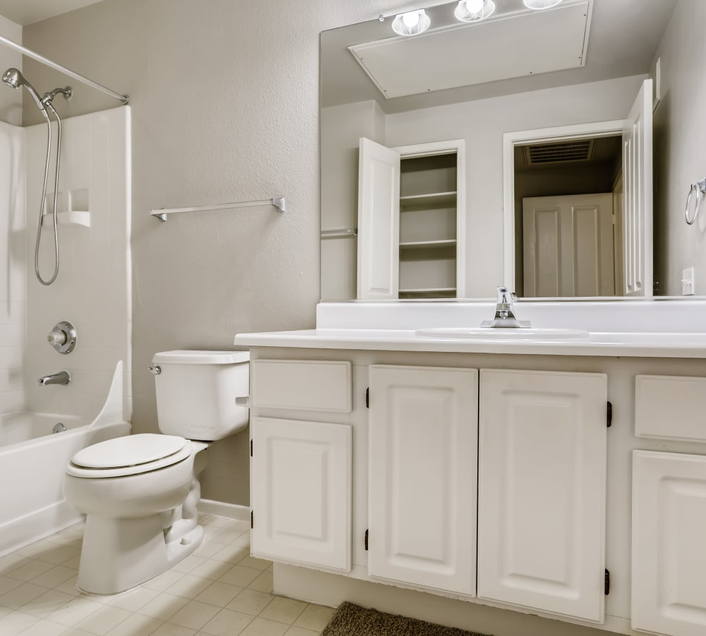 Standard bathroom with a large vanity mirror at Alicante Apartment Homes in Aliso Viejo, California