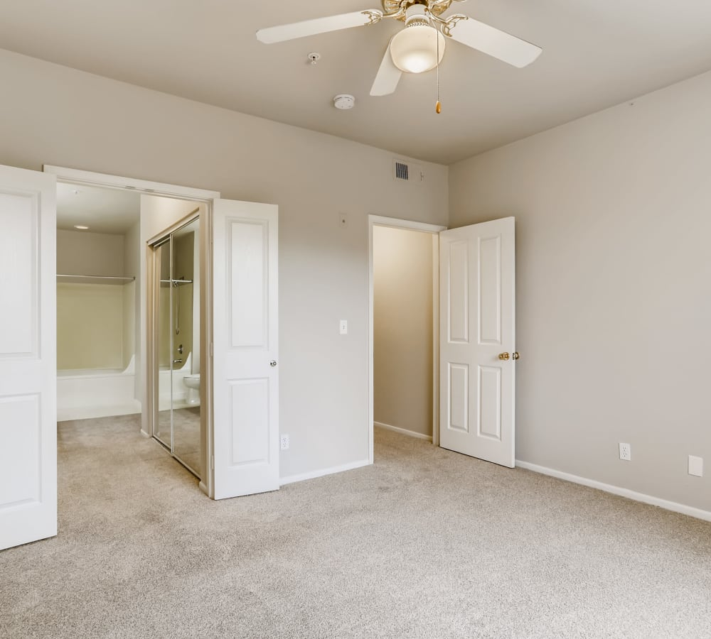Spacious bedroom with plush carpeting and a ceiling fan at Alicante Apartment Homes in Aliso Viejo, California