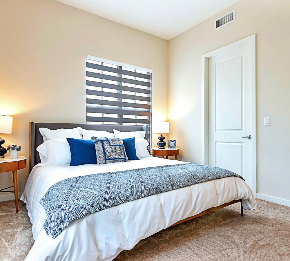 Carpeted bedroom with large closet next to the bed and tons of light at 6600 Main in Miami Lakes, Florida