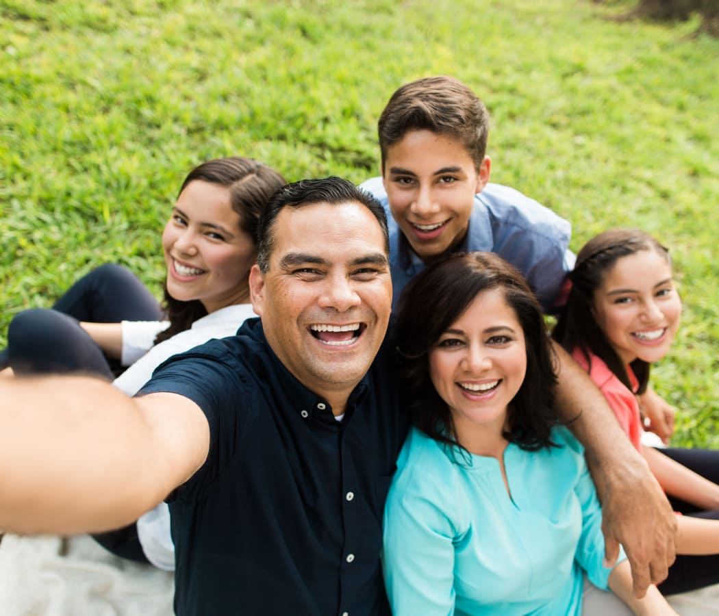 Family taking a selfie in the outdoor area at Creekside Place Apartment Homes in Thornton, Colorado