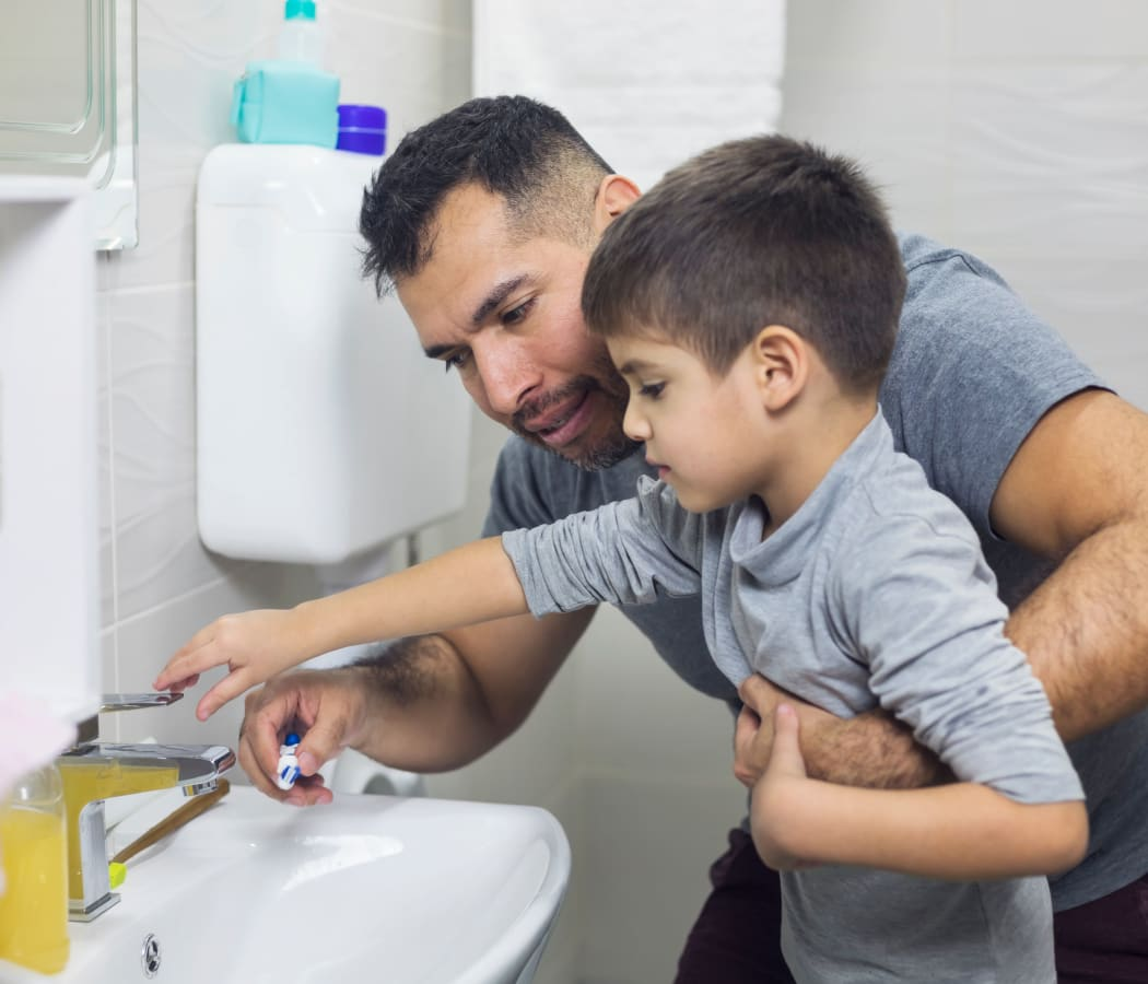 Dad helping his son get ready for bed at Creekside Place Apartment Homes in Thornton, Colorado
