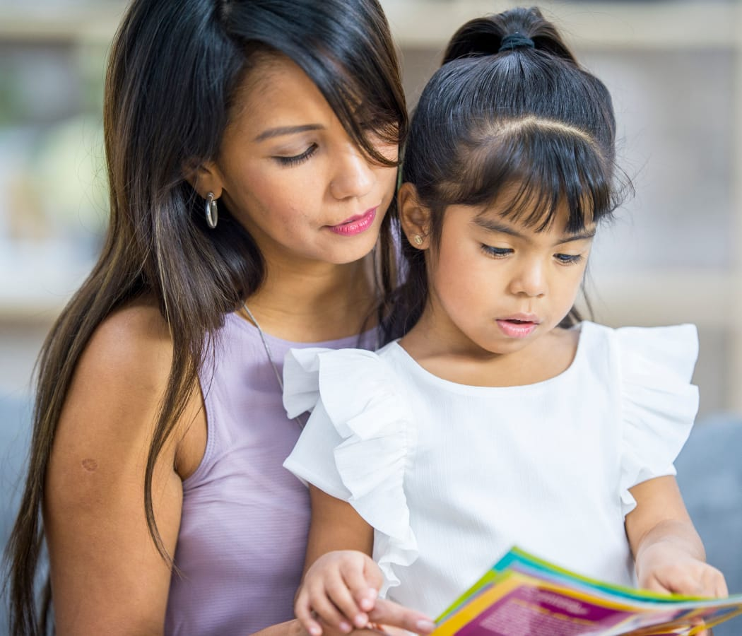 Mom and daughter reading a book in their Creekside Place Apartment Homes in Thornton, Colorado