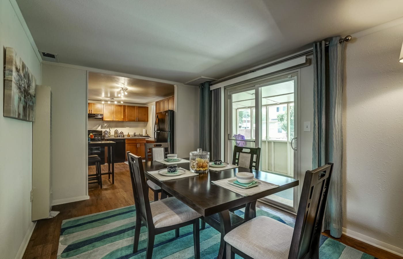 Dining area with kitchen in background in model townhome at Avalon Townhomes in Hampton, VA