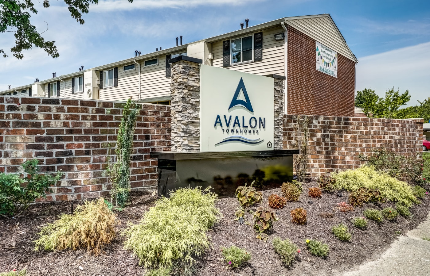 View of Avalon Townhomes' sign and well-manicured landscaping in Hampton, VA