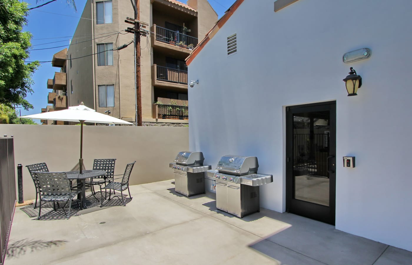 Barbecue grills and shaded seating outside at IMT Magnolia in Sherman Oaks, CA