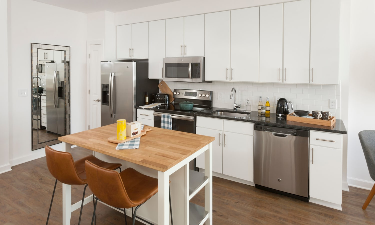 Island and white cabinetry in a model home's kitchen at The Bixby in Washington, District of Columbia
