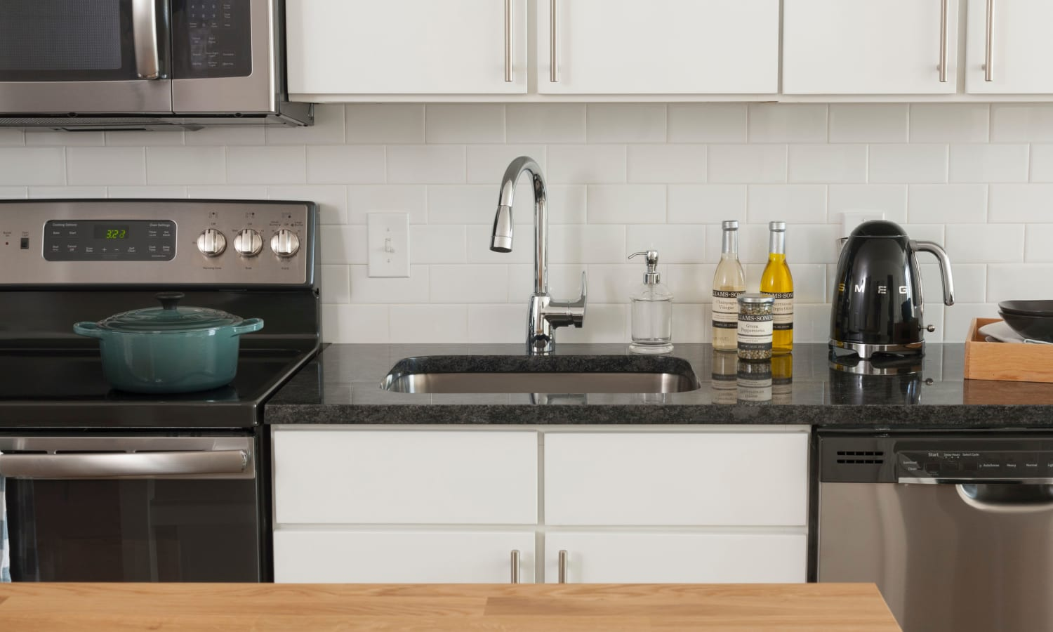 Granite countertops and subway tile backsplash in a model home's kitchen at The Bixby in Washington, District of Columbia