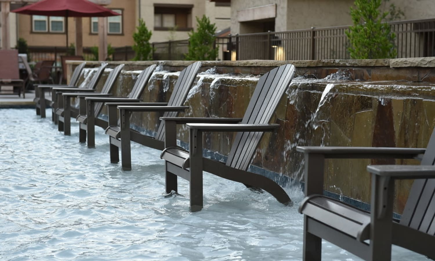 A row of chairs in water by the pool at Overlook Ranch in Fort Worth, Texas