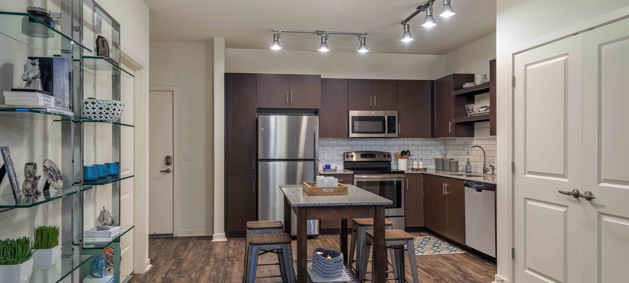 Dark wood cabinetry and hardwood floors in model home's kitchen at Capital Place in Phoenix, Arizona
