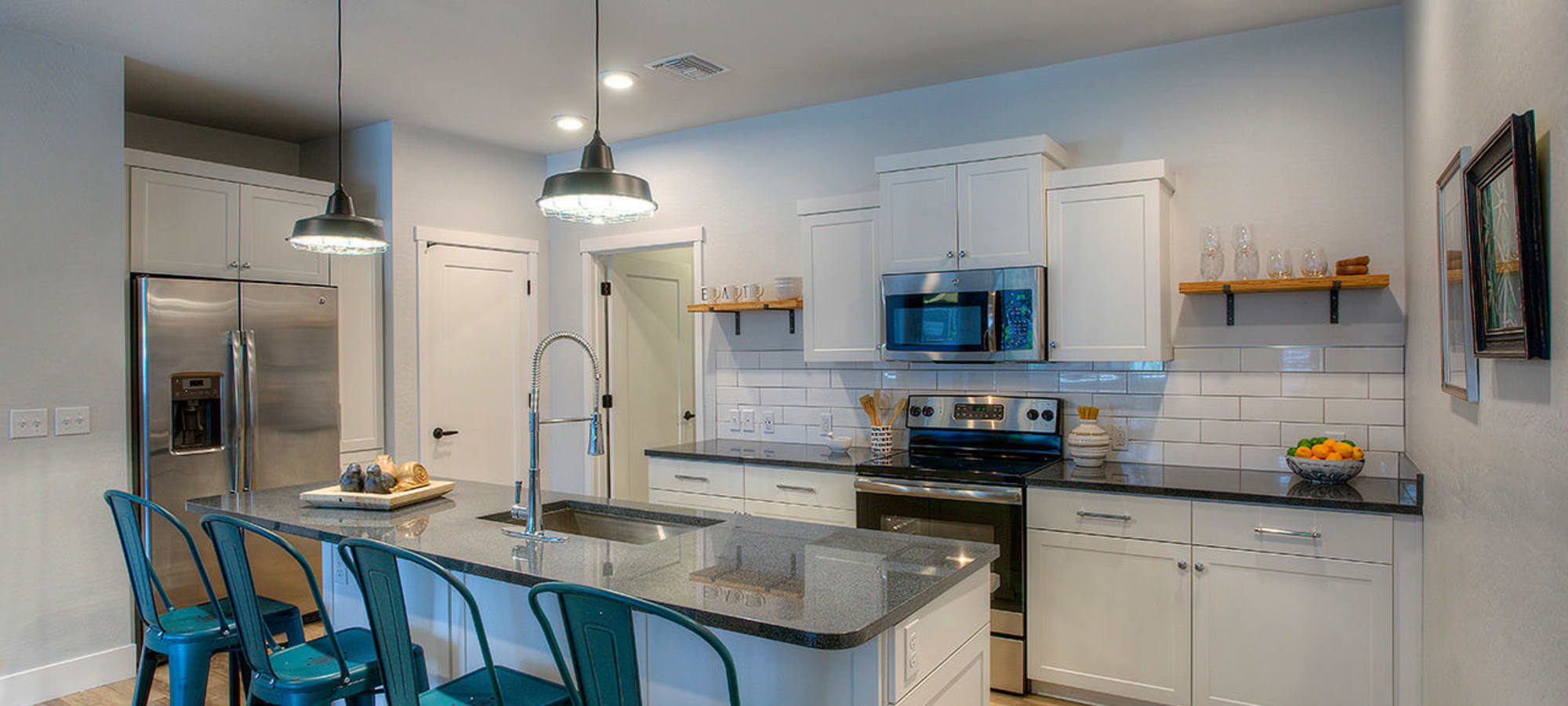 Gourmet kitchen with island, granite countertops, and energy-efficient appliances in model home at District Lofts in Gilbert, Arizona