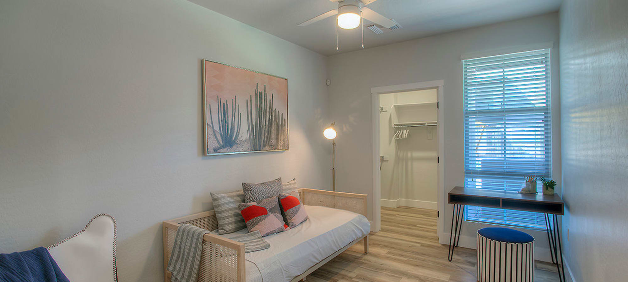 Guest bedroom with ceiling fan and walk-in closet in model home at District Lofts in Gilbert, Arizona