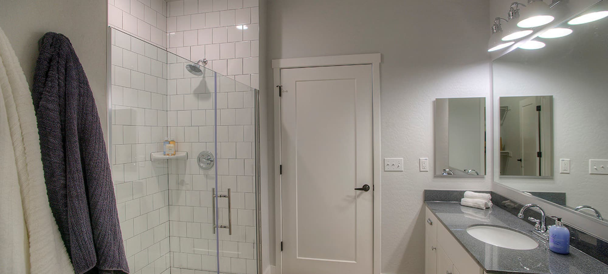 Large bathroom with tiled shower and granite countertop in model home at District Lofts in Gilbert, Arizona