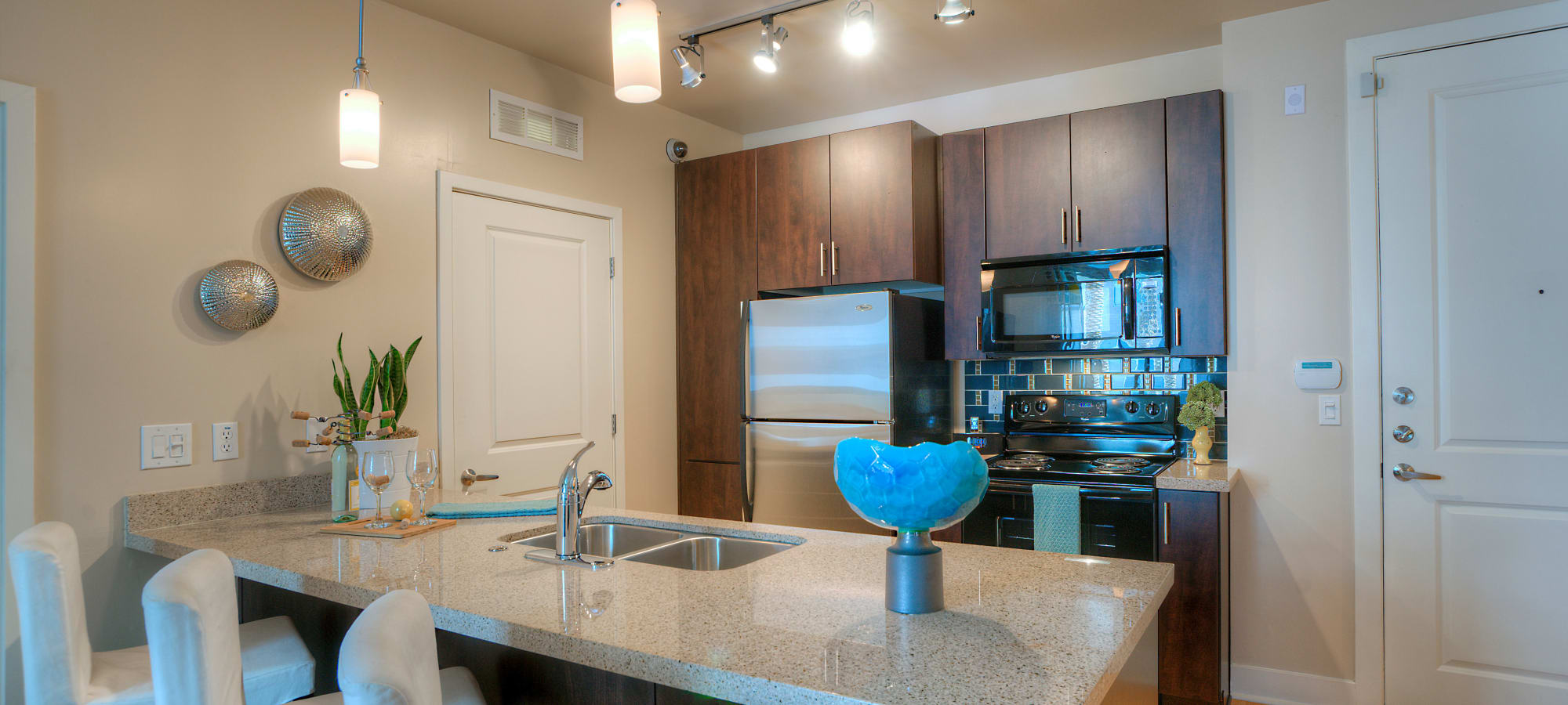 Granite countertops and stainless-steel appliances in model home's kitchen at Level at Sixteenth in Phoenix, Arizona