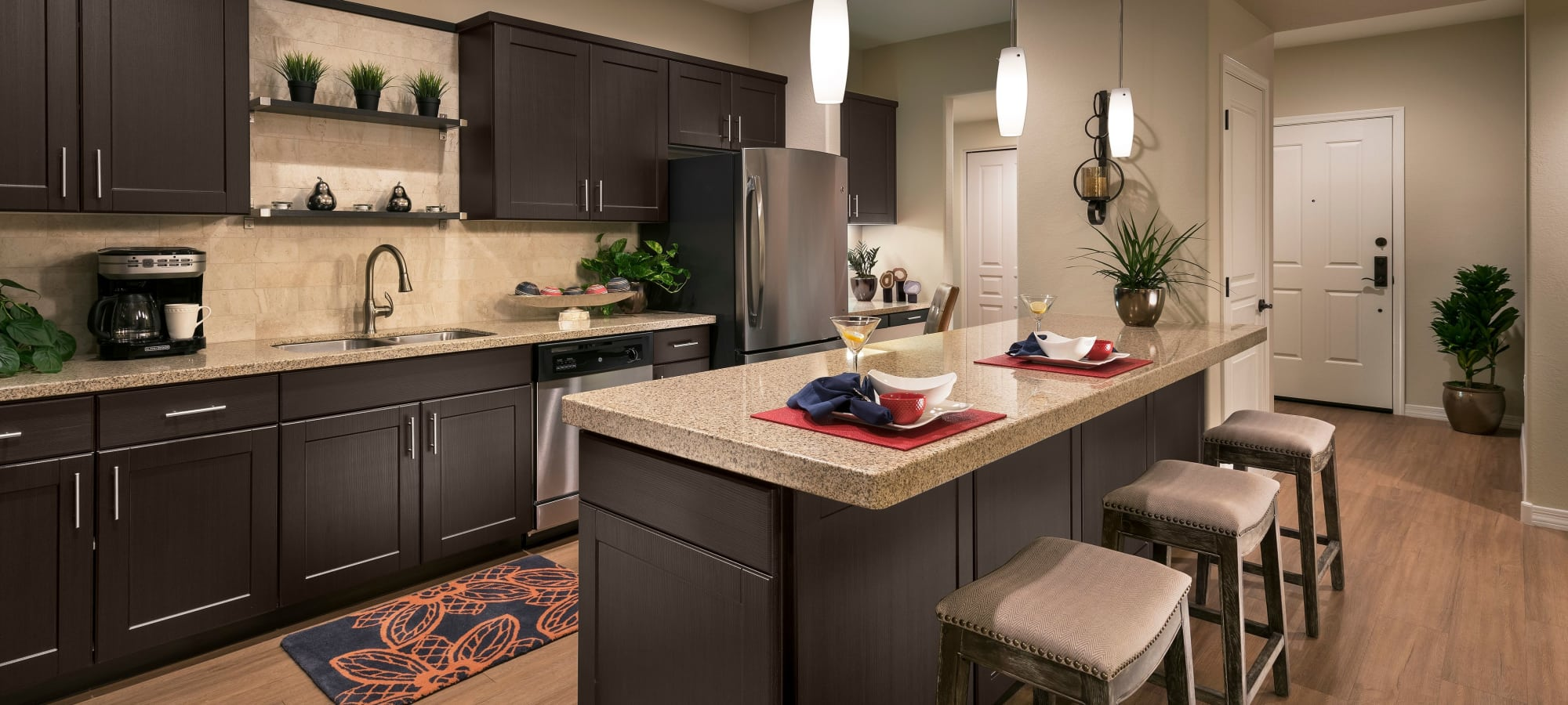 Gourmet kitchen with granite countertops and dark wood cabinetry in model home at San Milan in Phoenix, Arizona