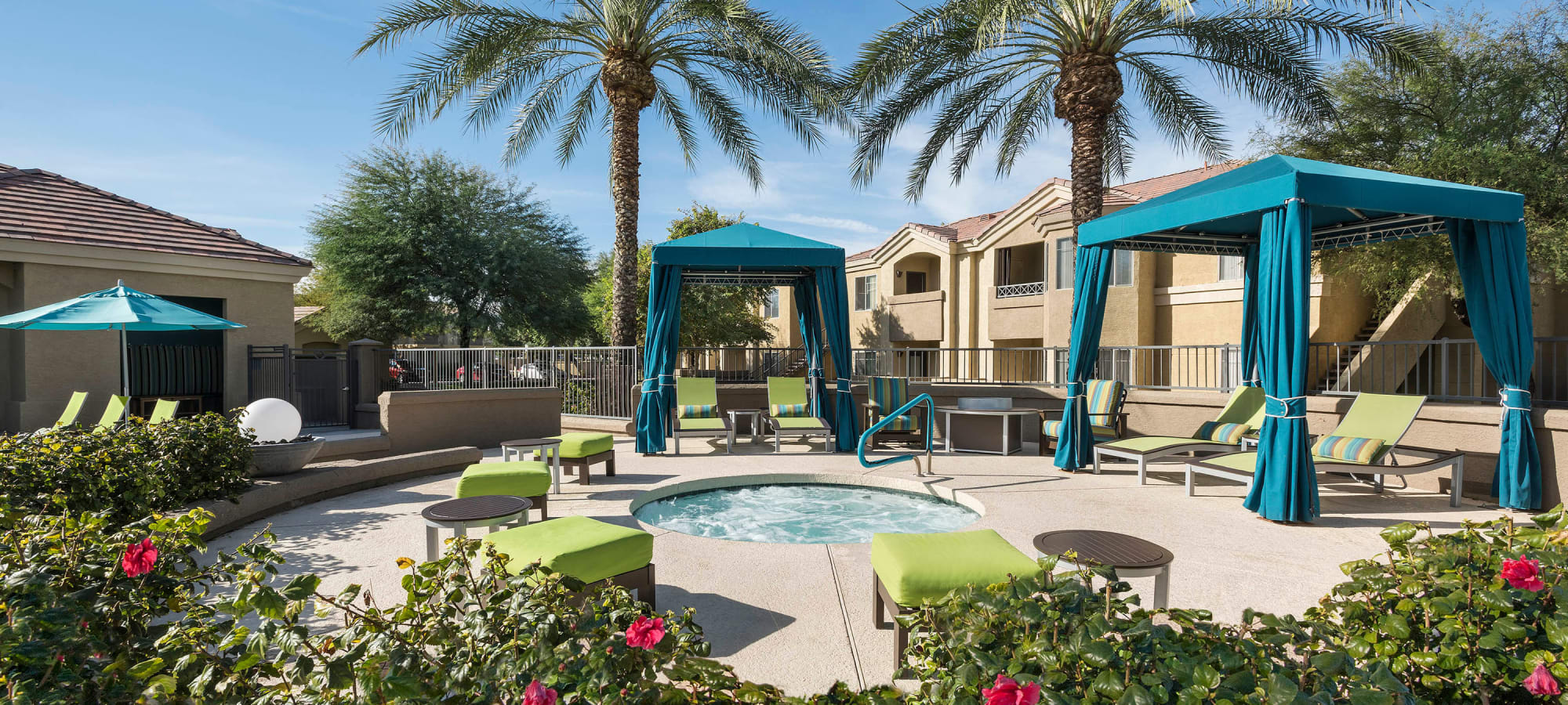 Spa with nearby shaded cabanas on a sunny day at Mira Santi in Chandler, Arizona