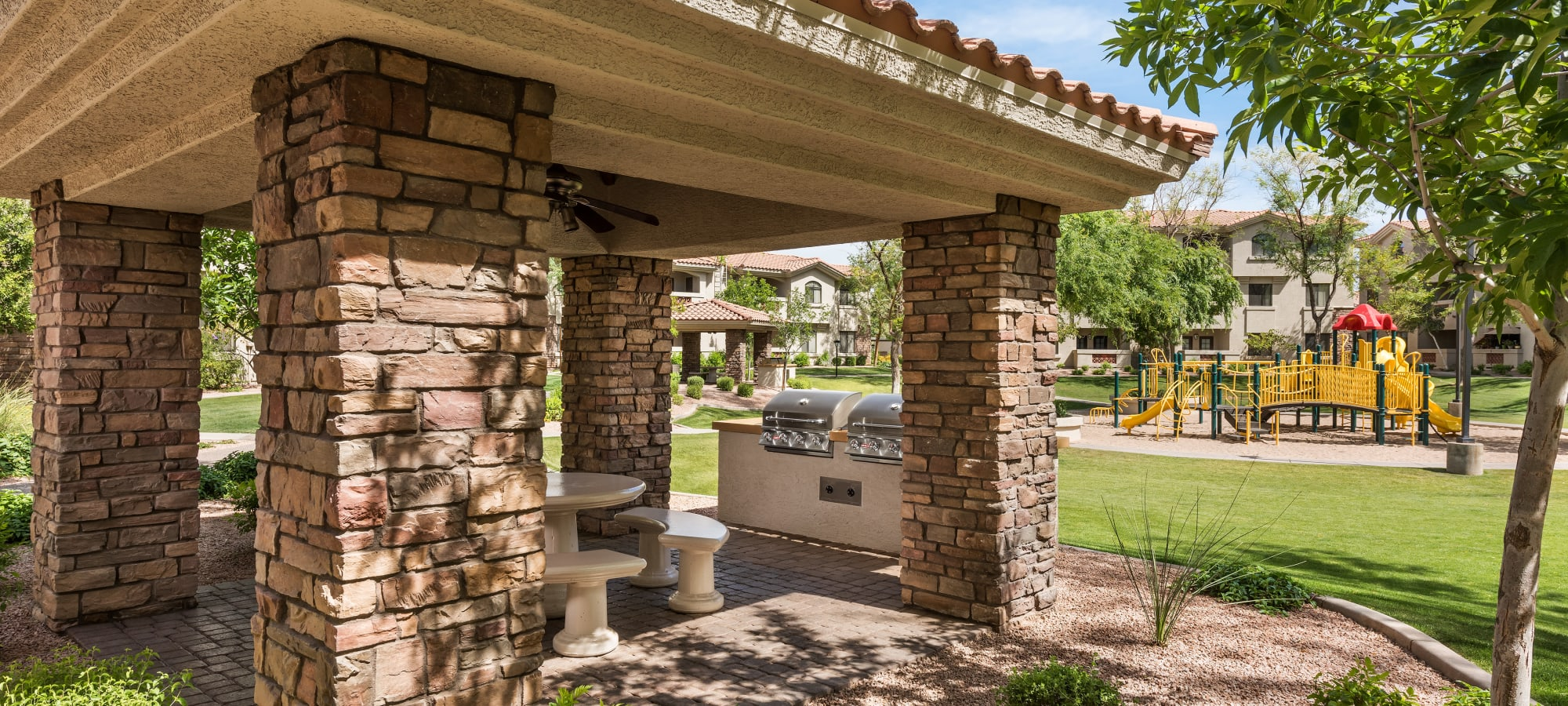 Covered BBQ grills and playground at San Hacienda in Chandler, Arizona