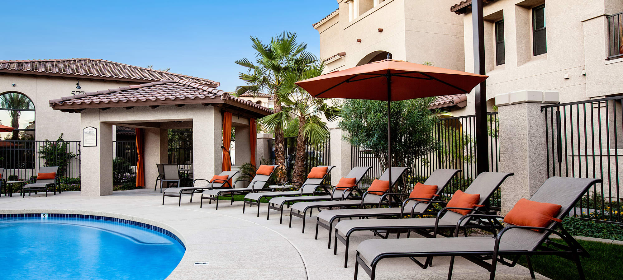 Chaise lounge chairs and umbrellas around the pool at San Marquis in Tempe, Arizona