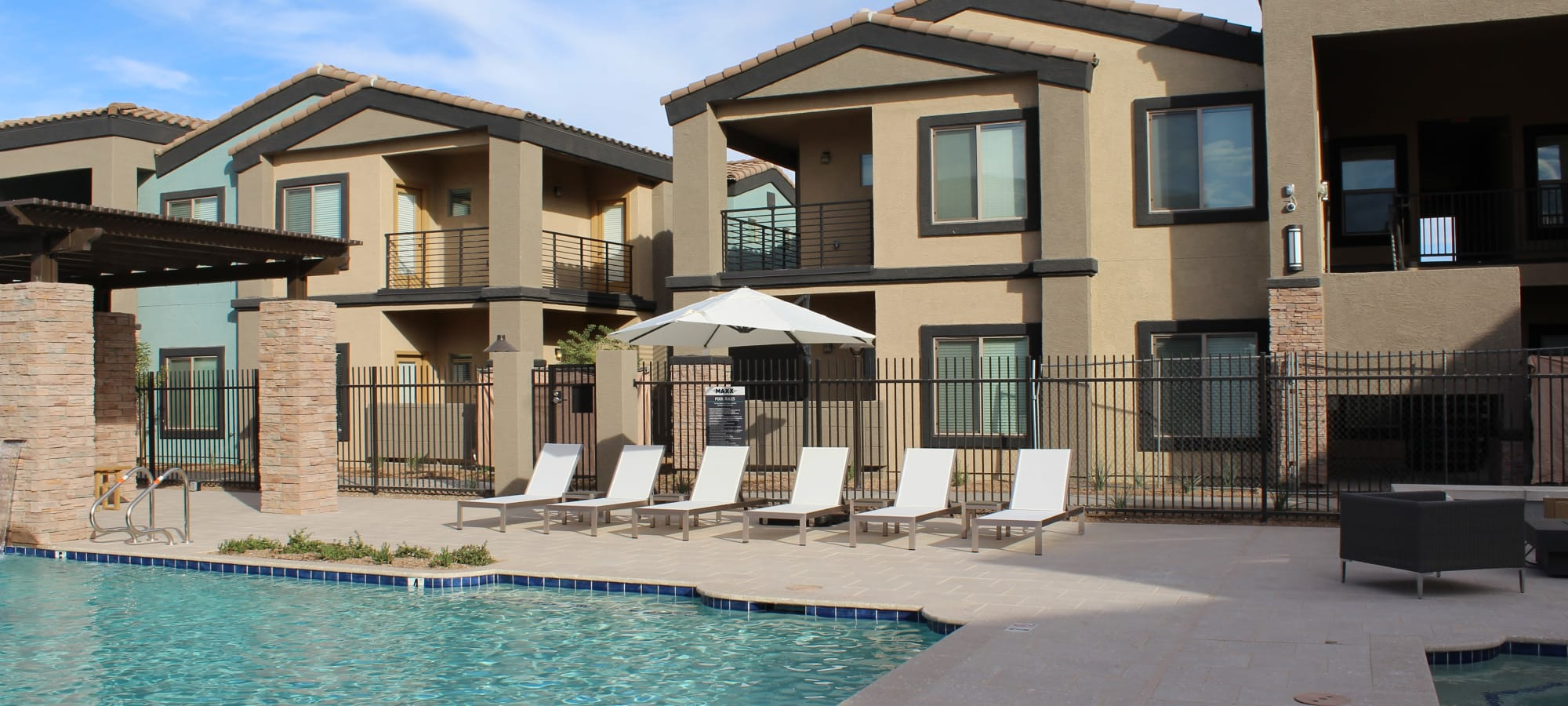 Swimming pool with lounge chairs at The Maxx 159 in Goodyear, Arizona