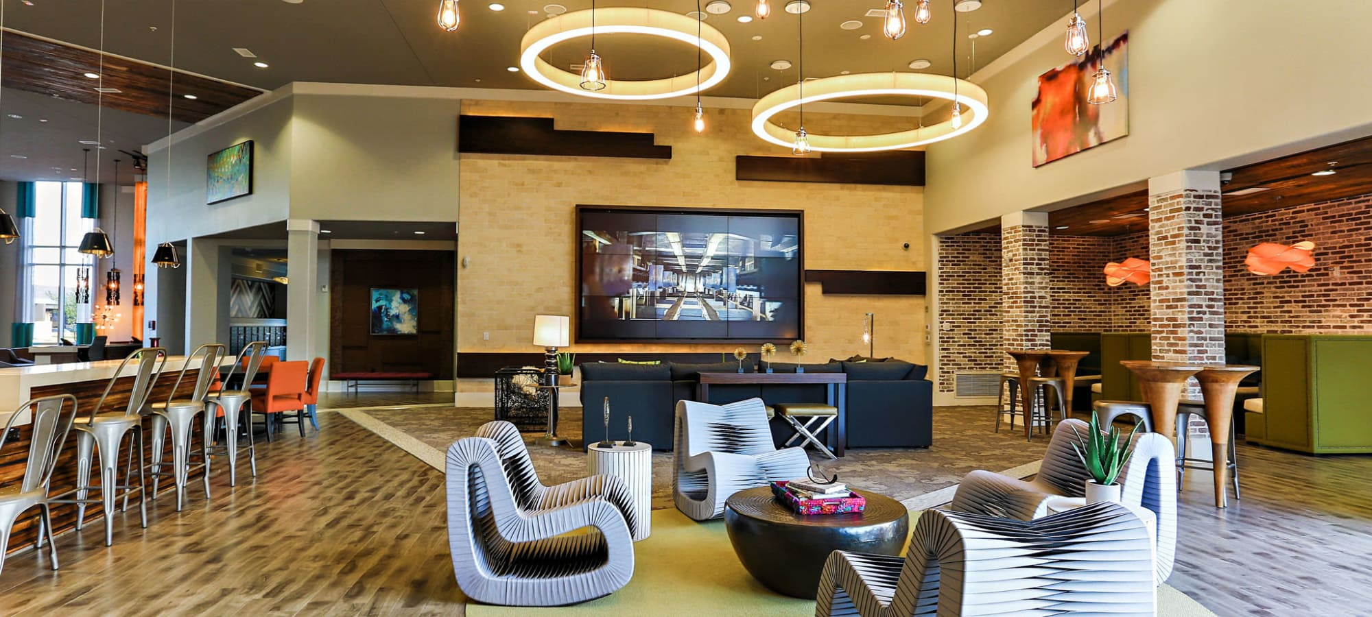 Comfortable seating in front of the large flatscreen TVs in the clubhouse at The Hyve in Tempe, Arizona