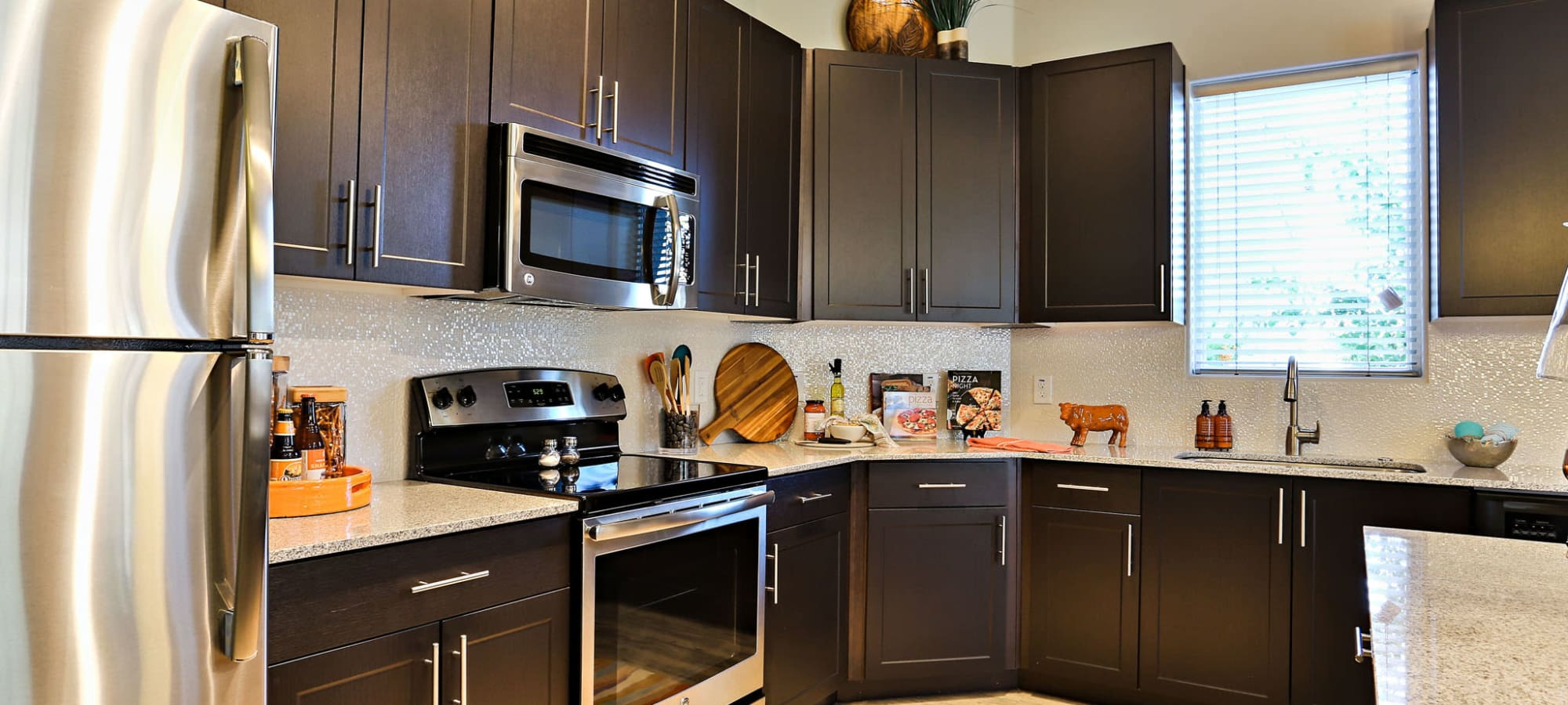 Stainless-steel appliances and dark wood cabinetry in model home's kitchen at The Hyve in Tempe, Arizona