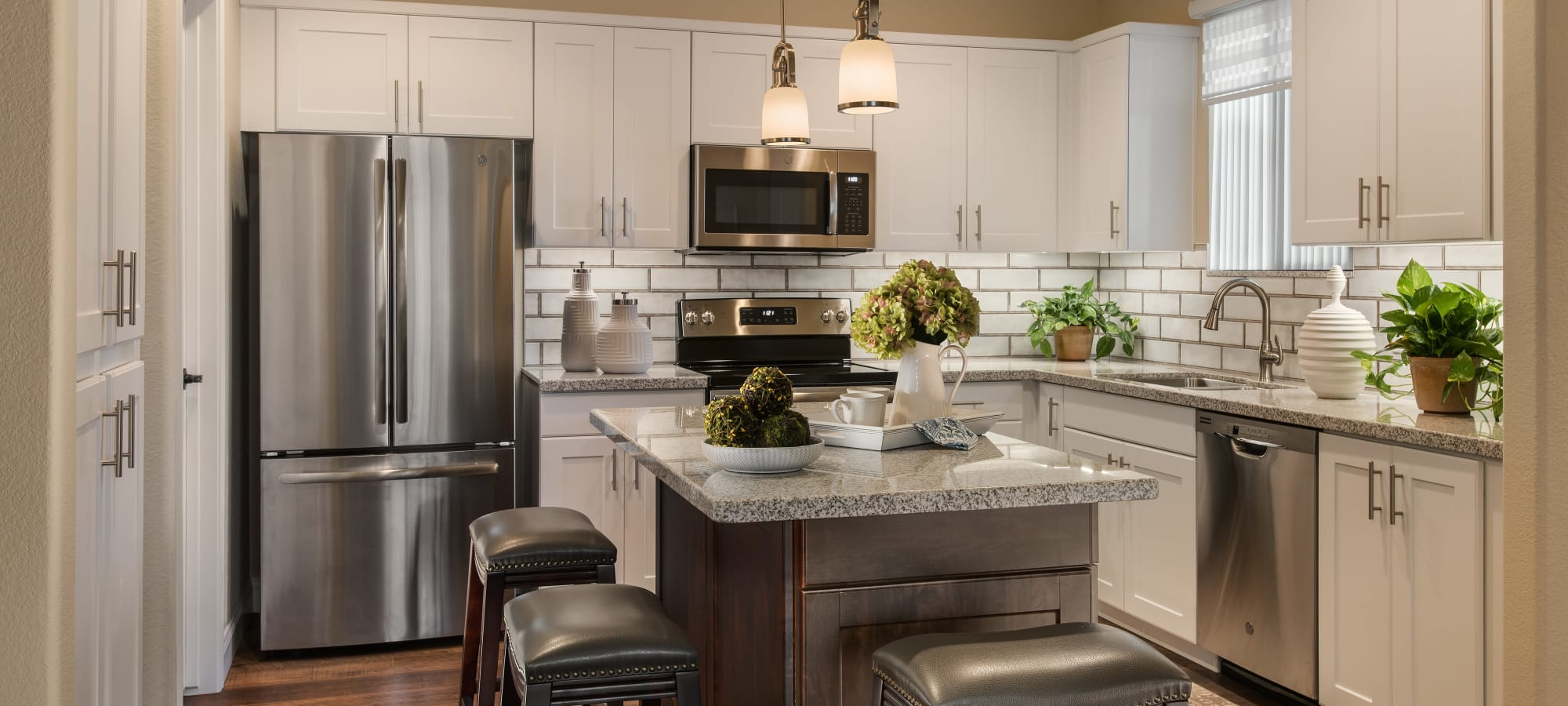 Modern kitchen with granite countertops and stainless-steel appliances in model home at San Piedra in Mesa, Arizona