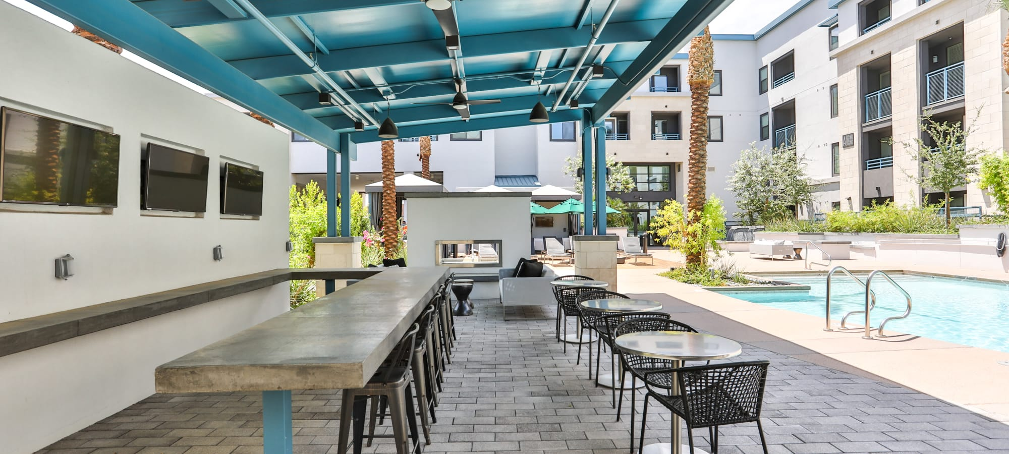 Outdoor bar seating with flat-screen TVs at Lakeside Drive Apartments in Tempe, Arizona