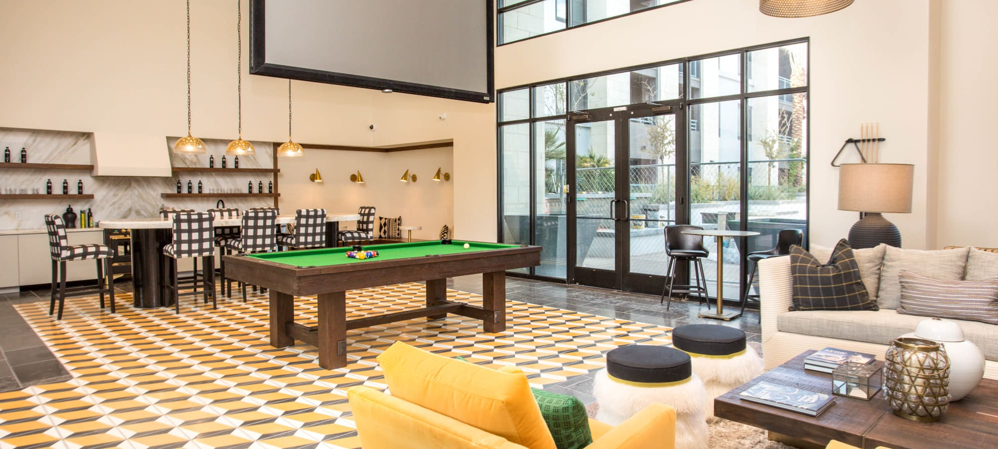 Large community clubhouse with a pool table and giant flat-screen TV at Lakeside Drive Apartments in Tempe, Arizona