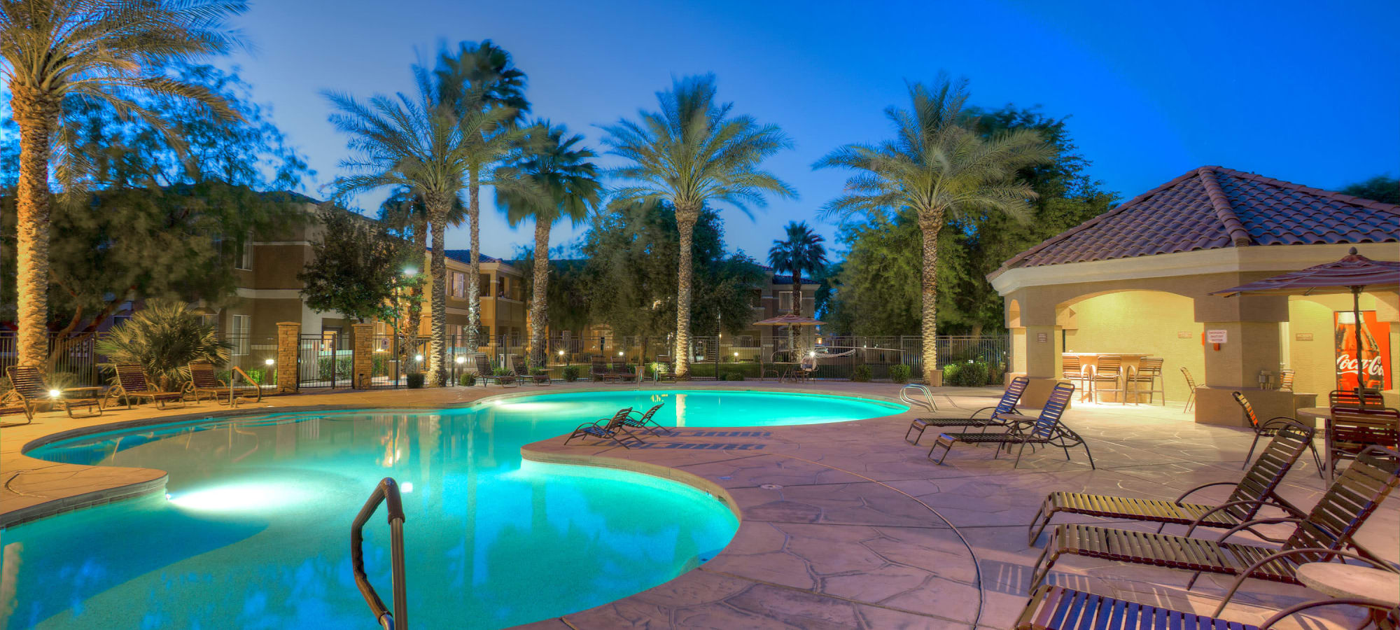 Night shot of the resort style swimming pool with lounge chairs at Remington Ranch in Litchfield Park, Arizona