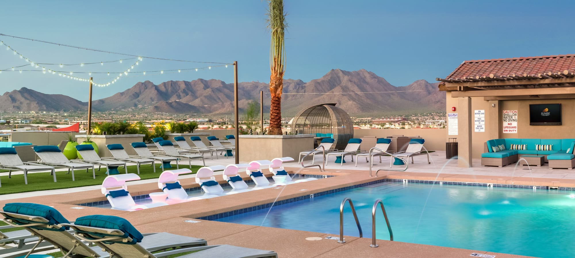 Resort-style swimming pool area with the McDowell Mountain range in the background at The Core Scottsdale in Scottsdale, Arizona