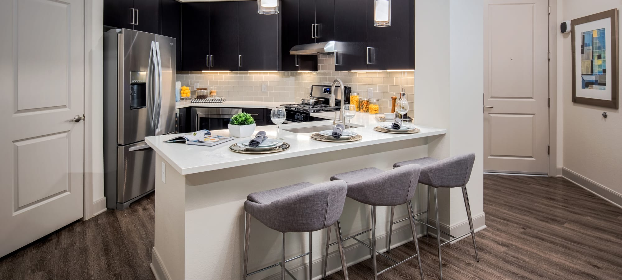 Island with breakfast bar in a model home's kitchen at The Core Scottsdale in Scottsdale, Arizona
