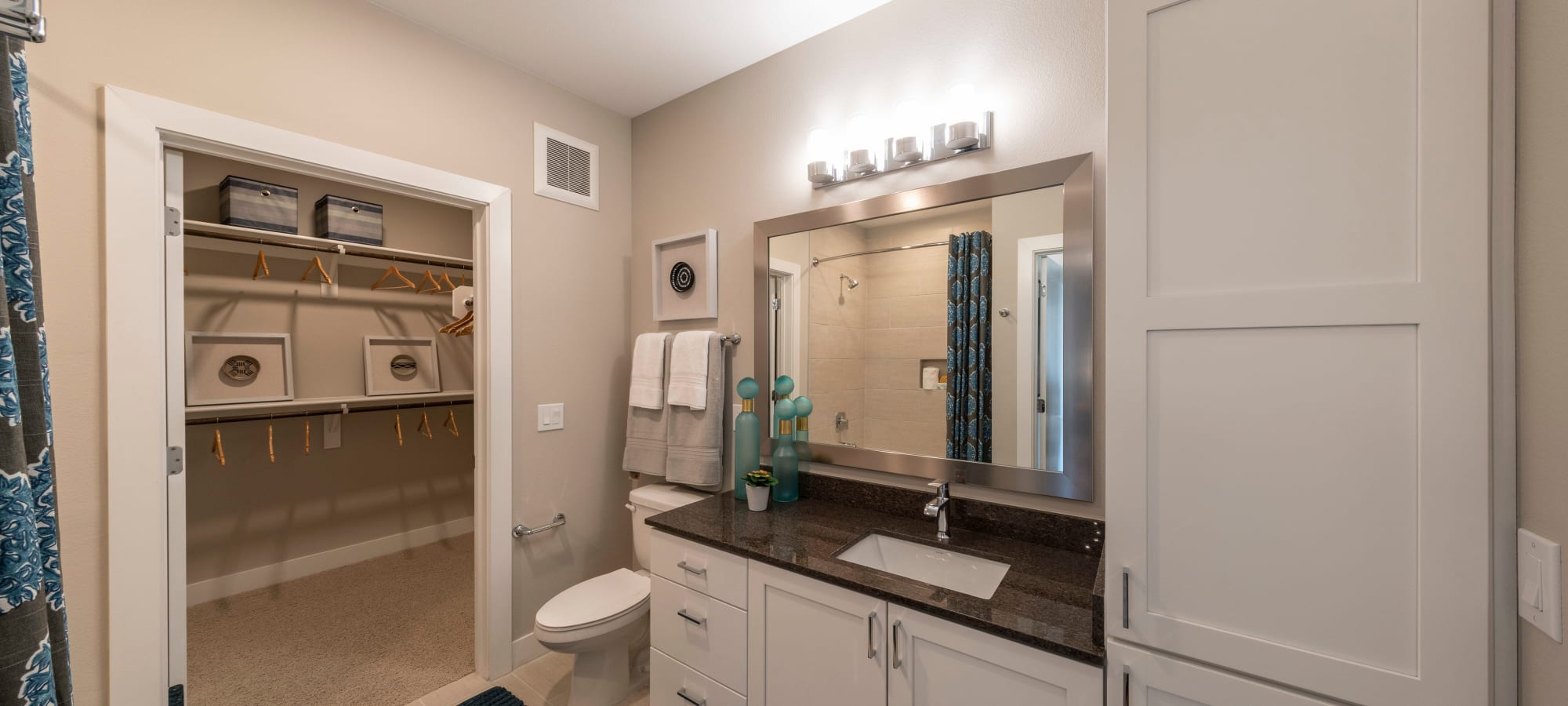 Bathroom with adjacent walk-in closet in a model home at Carter in Scottsdale, Arizona
