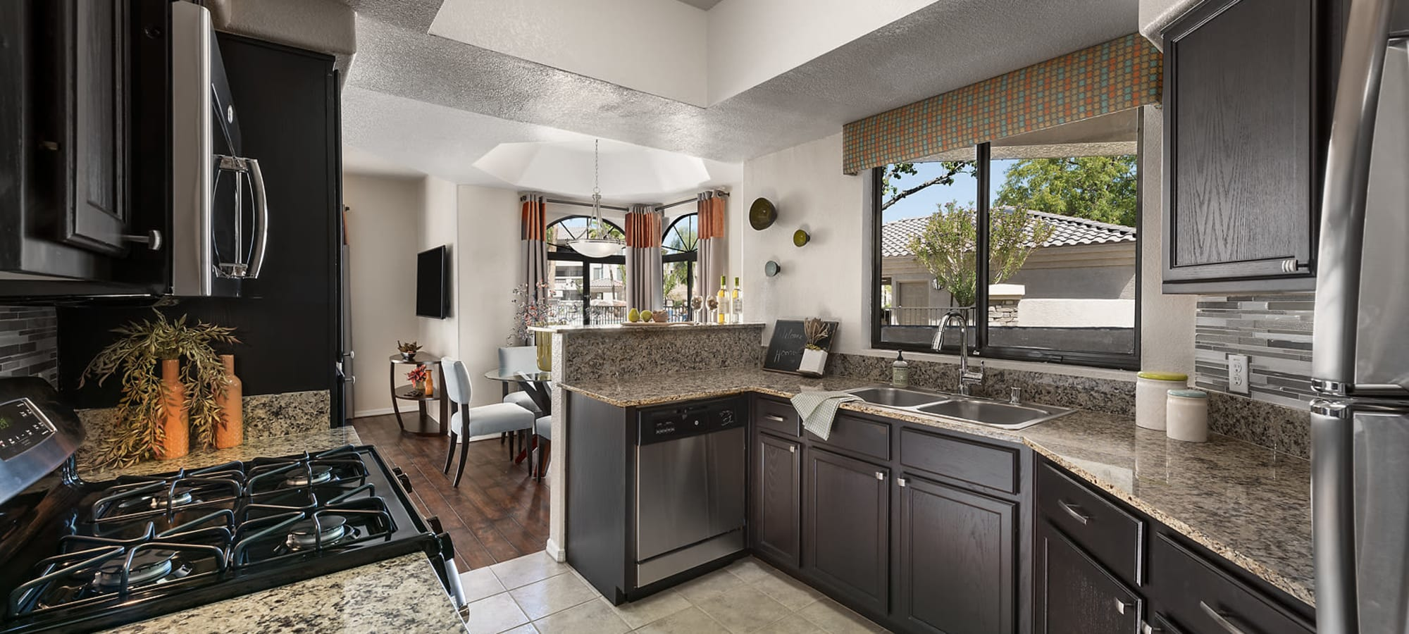 Gorgeous upgraded kitchen with granite and stainless steel appliances in a model home at San Pedregal in Phoenix, Arizona
