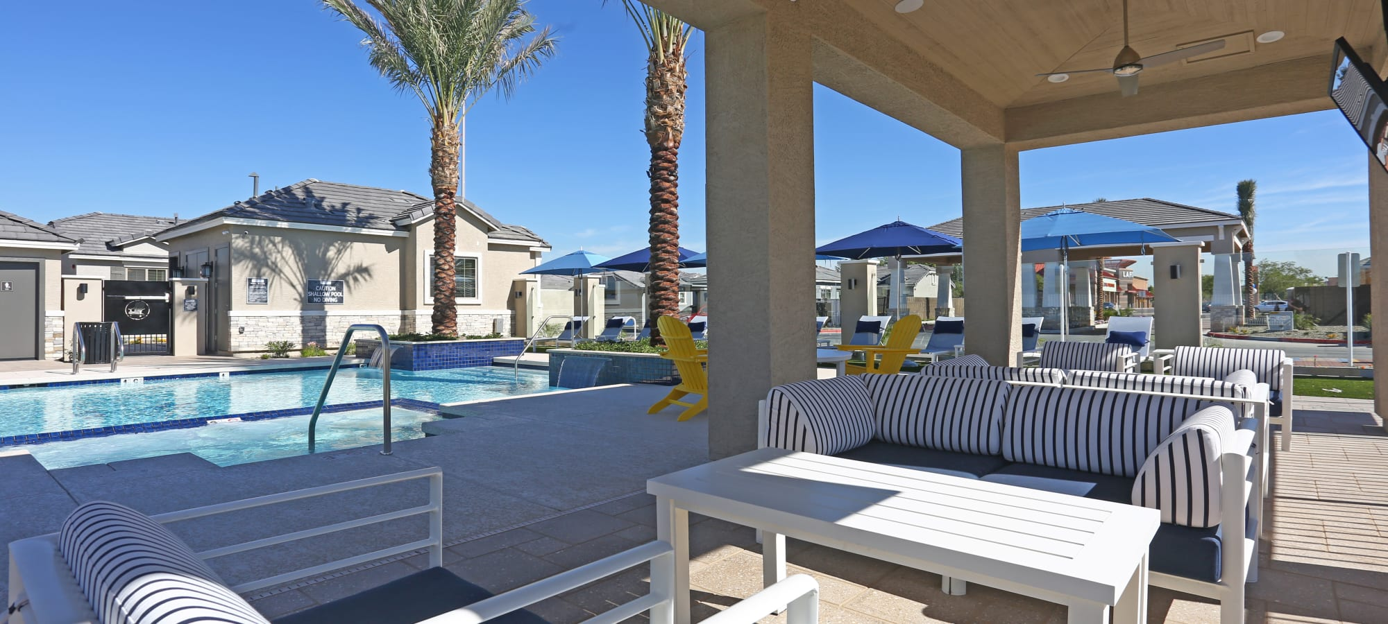 Lounge seating near the pool at Christopher Todd Communities At Estrella Commons in Goodyear, Arizona