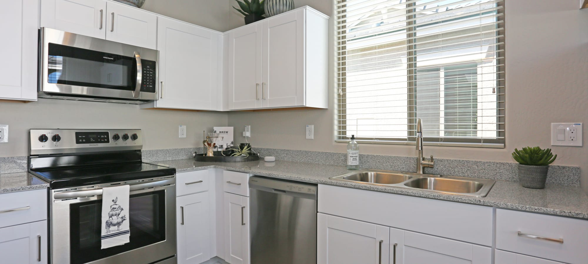 White cabinetry in the kitchen of a model home at Christopher Todd Communities At Estrella Commons in Goodyear, Arizona