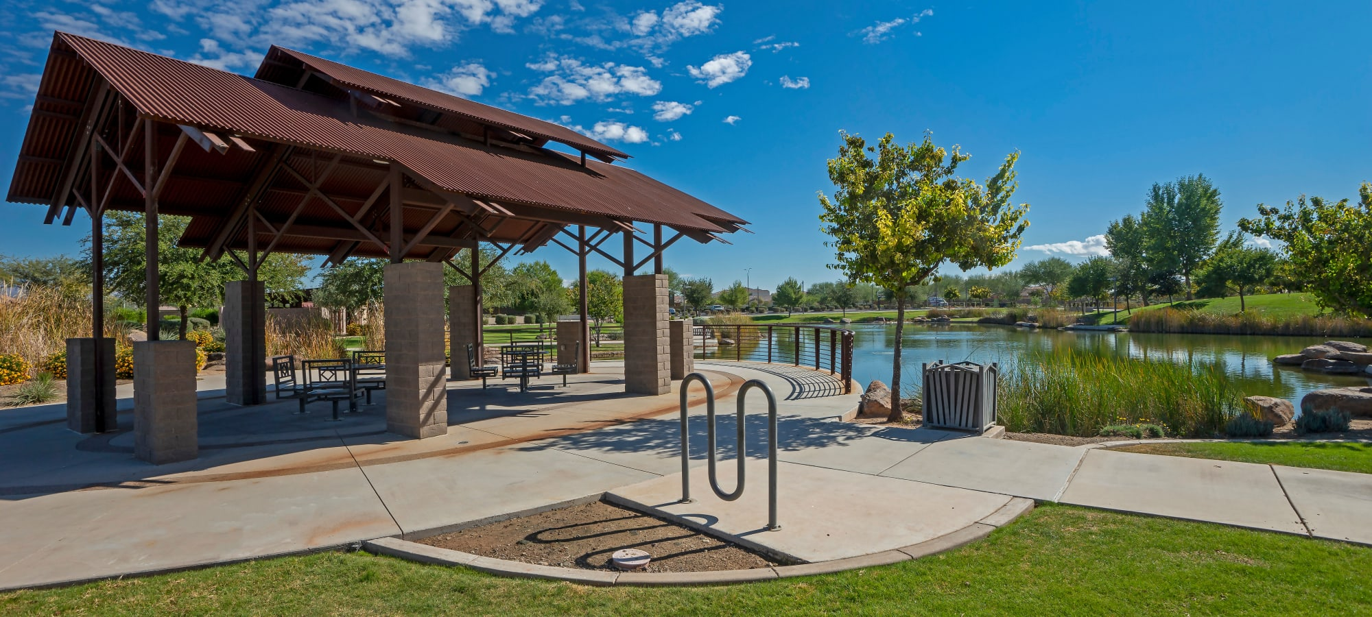 Outdoor covered seating by pond at BB Living at Eastmark in Mesa, Arizona