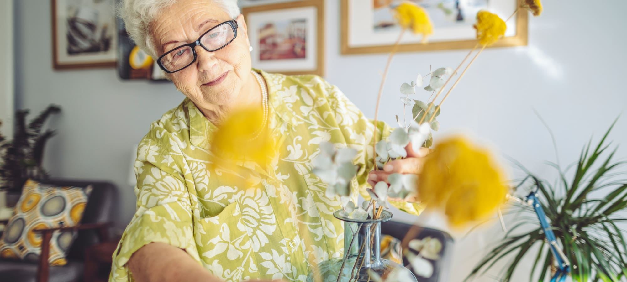 Woman in yellow shirt arranging yellow flowers in her apartment