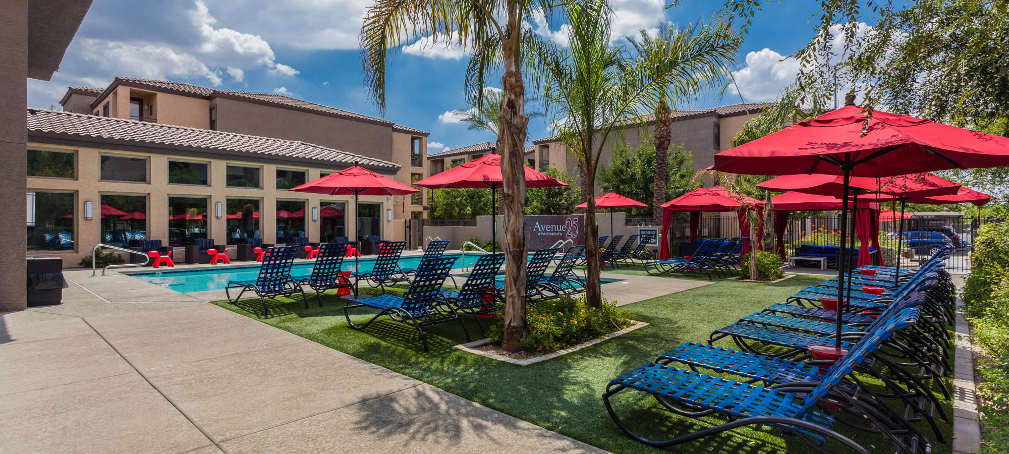 Covered outdoor seating by the pool at Avenue 25 Apartments in Phoenix, Arizona
