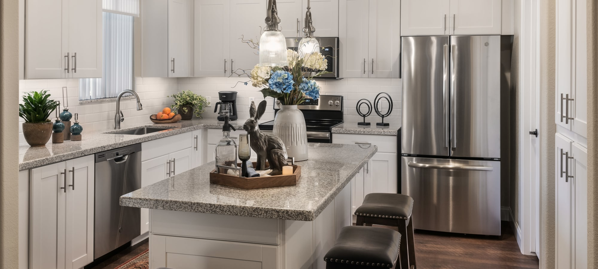 Modern kitchen with granite countertops and stainless-steel appliances in model home at San Villante in Mesa, Arizona