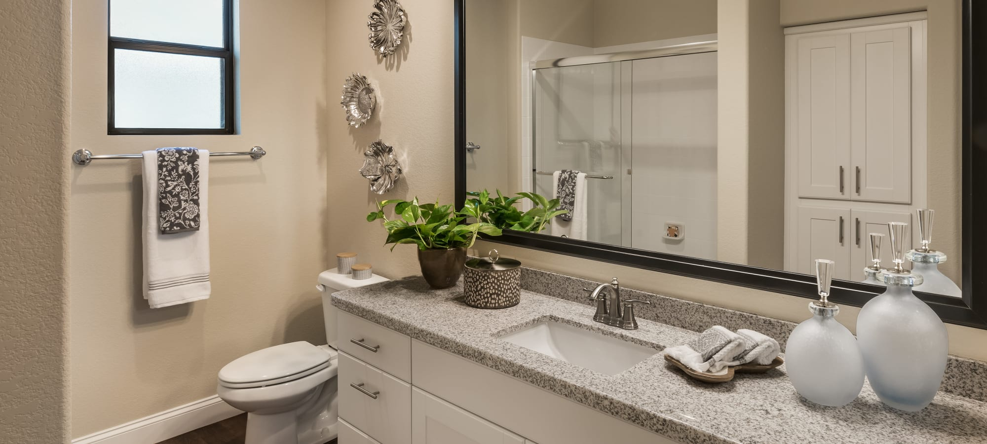 Large vanity mirror and granite countertop in bathroom of model home at San Villante in Mesa, Arizona