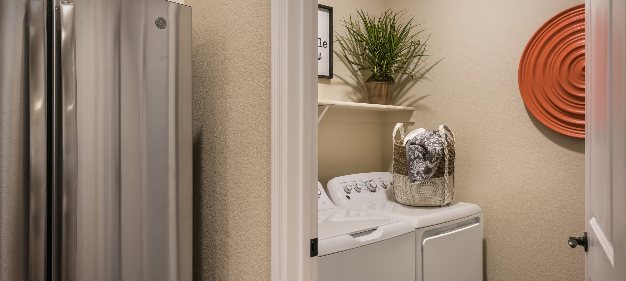 Washer and dryer area in stylish apartment  at San Villante in Mesa, Arizona