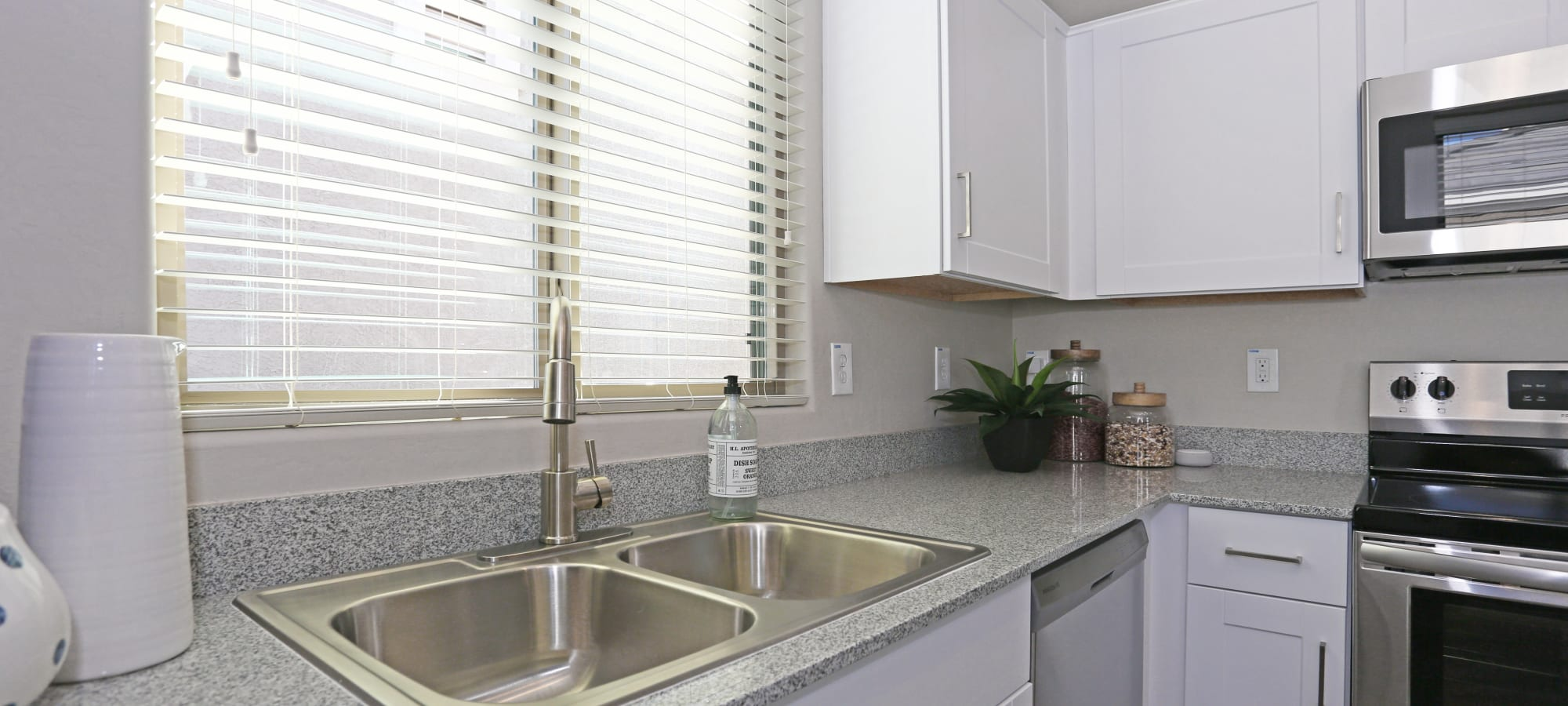 Dual stainless-steel sink in kitchen of model home at Christopher Todd Communities On Mountain View in Surprise, Arizona