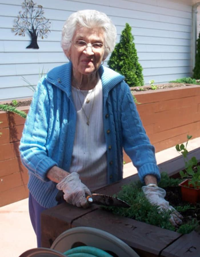 Resident standing at a planter with a hoe at Heritage Hill Senior Community in Weatherly, Pennsylvania