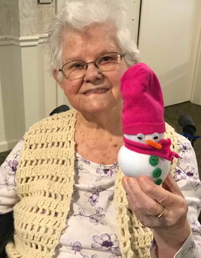 Resident holding a small snowman with a pink hat at Heritage Hill Senior Community in Weatherly, Pennsylvania