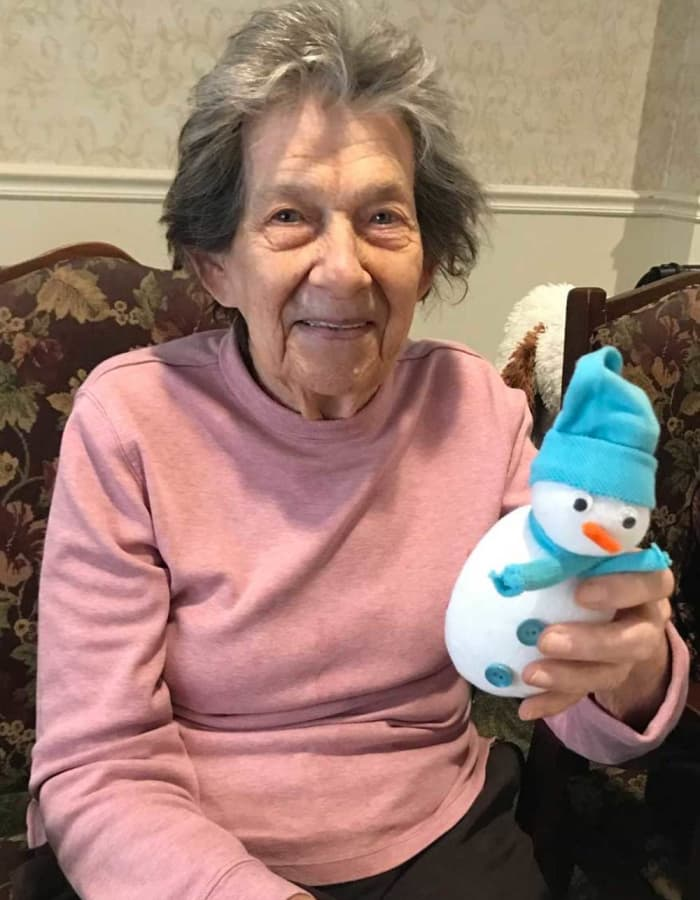 Resident holding a small snowman at Heritage Hill Senior Community in Weatherly, Pennsylvania