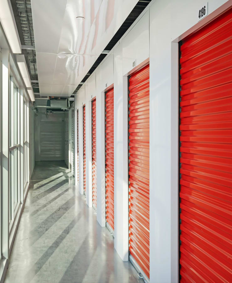 Indoor storage units with red doors at StorQuest Self Storage in Paramount, California